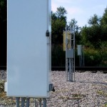 Pole mounted AEI sites reduce the total costs of an AEI site installation by as much as $600 and saves space, the trade off is no AC, reduced back up power, no way to get out of the weather during maintenance, and less protection from vandalism.